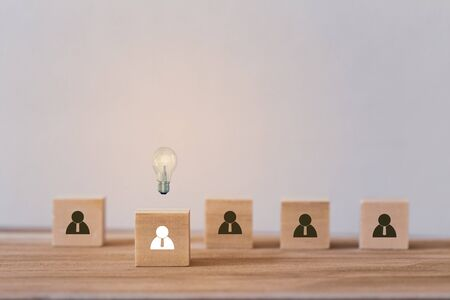 Creative idea and innovation concept: leader with idea and innovation. Wood block with human symbol and light bulb icon