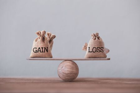Gain and loss bags on a basic balance scale on blackboard. Capital investment gain and loss, financial concept, depicts balancing between profit and loss while managing assets e.g bonds, stocks, derivatives, ETFs