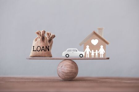 Loan bags with family member and car in a house on balance scale. Concept family financial management, mortgage and payday loan or cash advance.