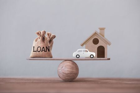 Loan bags, wood home with car in a house on balance scale. Concept family financial management, mortgage and payday loan or cash advance.