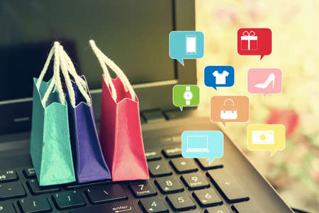 Paper shopping bags on laptop keyboard. depicts online shopping. e-commerce or electronic commerce is a transaction of buying or selling goods or services online over the internet.