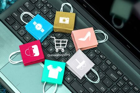 Online shopping on website, Paper shopping bags on notebook keyboard. depicts online shopping or order goods on the internet It is more popular. can buy everything from home or office.
