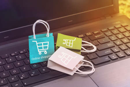 Online shopping on website, paper shopping bags on notebook keyboard. business concept about online shopping or order goods on the internet It is more popular. can buy everything from home or office.