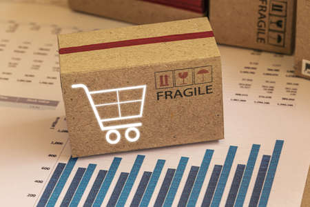 Small cardboard box with printed words for logistics. This type of financial charts include stacks of bar compare between the expansion of export business and increase the rate of goods each year. 免版税图像