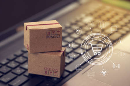 Shopping online, e-commerce concept: Cardboard boxes with icon customer network connection on keyboard. depicts of transportation that can be done easily using an online internet. 免版税图像