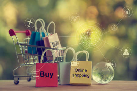 Shopping Online and e-commerce concept: Paper bag in a shopping cart and crystal globe. Online stores are considered as another medium of trading goods between entrepreneurs and customers. 免版税图像