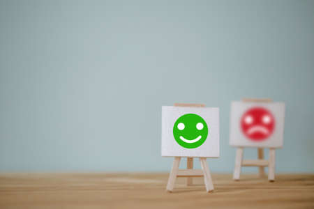 Satisfaction survey concept: Sign stand with a smiley face on wood table. depicts the best excellent business services rating customer experience.