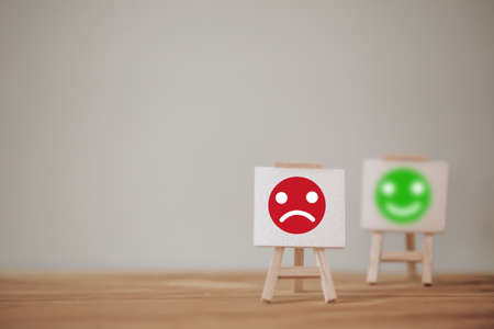 Satisfaction survey concept: Sign stand a sad face and a smiley face on wood table. depicts the best excellent business services rating customer experience.