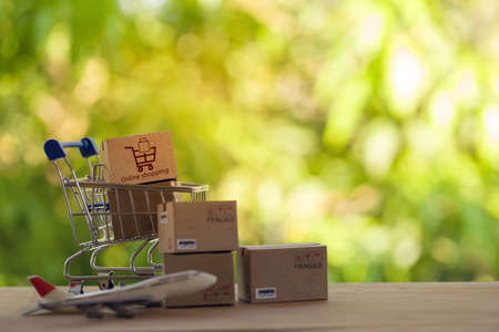 Paper boxes in shopping cart on the notebook keyboard. Shopping Online / e-commerce or electronic commerce is a transaction of buying or selling goods or services online over the internet.