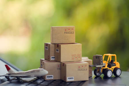 Logistic and cargo freight concept: Fork-lift a truck moves a paper box on notebook keyboard in the natural green background. depicts  International freight or shipping service for online shopping. 免版税图像