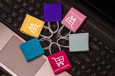 Colorful paper shopping bags put in circle around on notebook keyboard. business concept of online shopping. e-commerce is a transaction of buying or selling products or services online internet. 免版税图像
