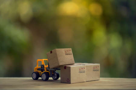 Logistic and cargo freight concept: Fork-lift a truck moves a paper box on table. depicts International freight or shipping service for online shopping.
