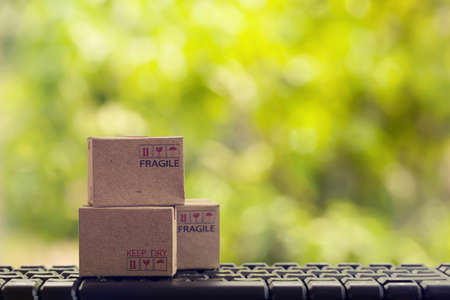 Cardboard box on notebook keyboard. Online shopping, e-commerce and delivery service concept. Product service and delivery to consumers by connecting with the internet.