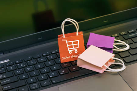 Small and colorful paper shopping bags on a laptop keyboard. Ideas about online shopping or shopping at home or office which customers can purchase items or services or goods remotely. Imagens