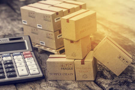 business concept: Cardboard boxes and calculator. Concept of Increasing product rates the expansion of export business to plan marketing or finance go future. Zdjęcie Seryjne