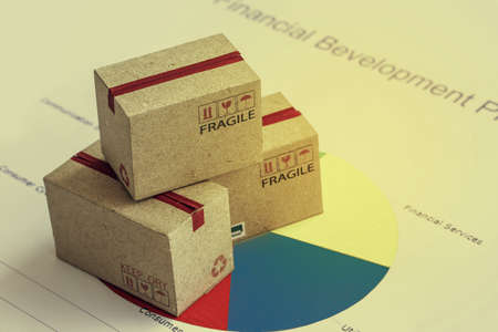 Closeup shot of three cardboard paper boxes and this type of financial charts include stacks of bar compare between the expansion of export business and increase the rate of goods each year. Archivio Fotografico