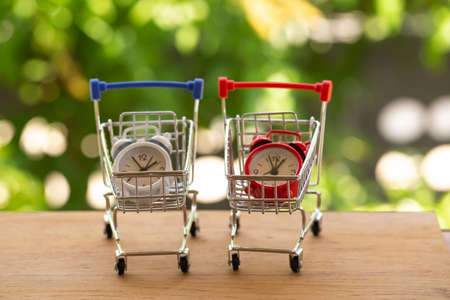 Analog clock in silver shopping cart or a supermarket shopping basket on wooden table. Fast delivery, time value of money concept : depicts the importance of time in our daily life. 版權商用圖片
