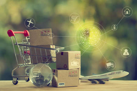 Shopping Online and e-commerce concept: Paper boxes in a shopping cart and crystal globe, plane. Online stores are considered as another medium of trading goods between entrepreneurs and customers.