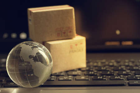 Shopping online, e-commerce concept: Crystal globe with cardboard boxes on keyboard. depicts of purchase of products on internet used for worldwide international connections.