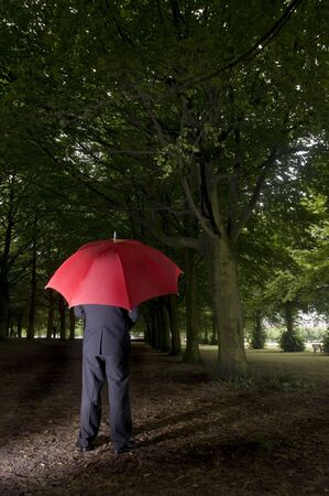 A business man holding an umbrella in a dark forest Stock Photo