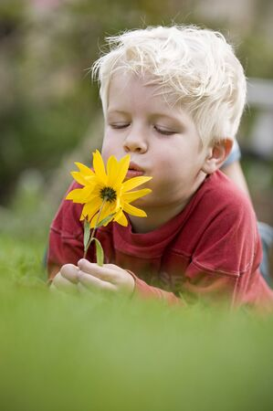 Infant boy smelling a flower and smiling in the camera