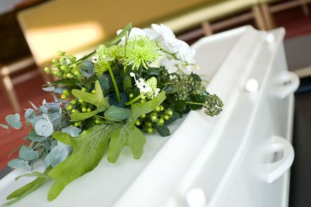 white casket with flowers