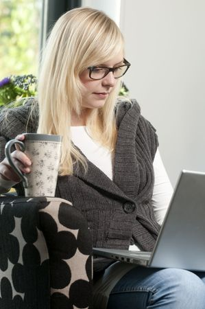 young woman with laptop and a cup of tea