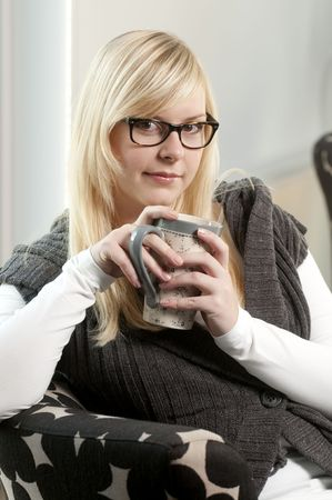young woman in the livingroom holding a cup of tea