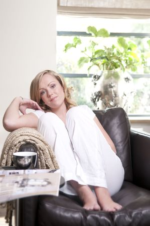 Young attractive woman relaxing in a sofa. Stock Photo