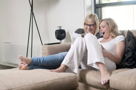 Two girlfriends on a sofa reading a magazine an laughing holding a remote control. Stock Photo