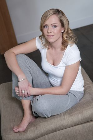 Young attractive woman relaxing on a sofa looking in the camera.