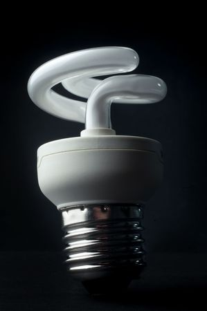 an energy saving  light bulb against a black background Stock Photo
