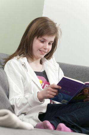 Una niña leyendo un libro en su casa.  Foto de archivo - 6615529
