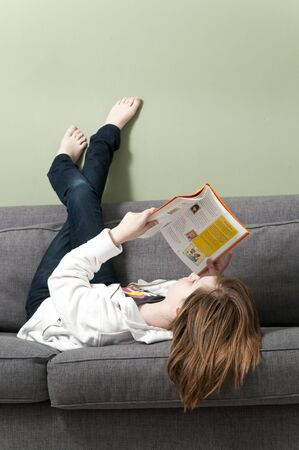 child book: A young girl reading a book at home. Stock Photo