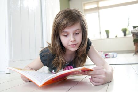 Girl lying on the floor of her house reading a book