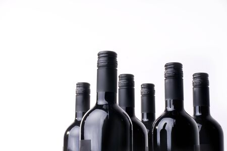 Dark wine bottles in a row against a white background.