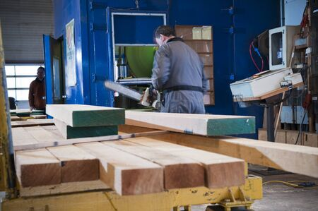 A man working with processed lumber at a sawmill
