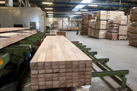 Lumber coming of the conveyer belt in a saw mill Stock Photo