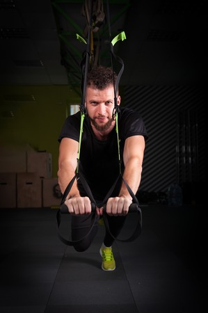 muscled: One young handsome brave curly bearded muscled man with a beard makes Total Resistance eXercises fitness trx straps working out in gym crossfit