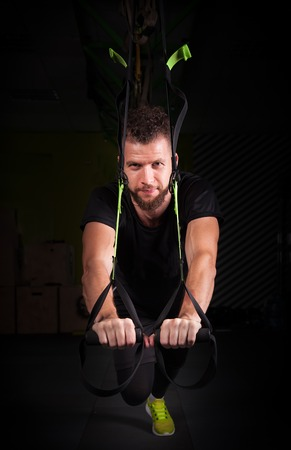 muscled: one handsome young muscled man training with trx while working out in gym