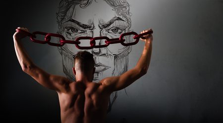 One young man in a black chain raises above his head. The concept of freedom, or sports. Free spase for comercial Grey background with copy space Stock Photo