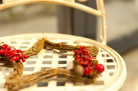 Wooden star of branches with clusters of red berries lying on a wicker chair