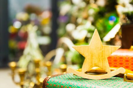 Christmas Fir Tree Toys Old wooden star It stands on an retro suitcase Burning Candles, Boxes, Balls, Pine Cones, Walnuts, Branchesin the background other decorations and garlands. copy space