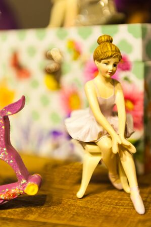 A small statue of a seated ballerina surrounded by boxes and other toys on a wooden table.