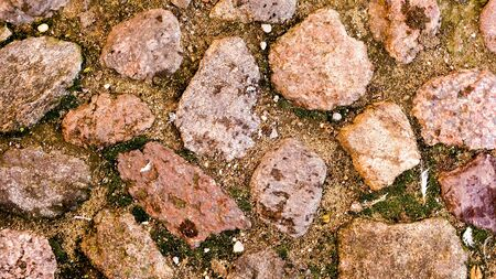 rough road: rough stones with sand around them at paved road, close-up shot