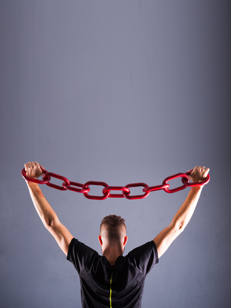 comercial: One young man in a black chain raises above his head. The concept of freedom, or sports. Free spase for comercial Grey background with room for text Stock Photo