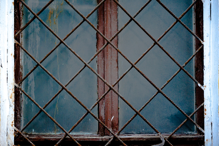 lattice window: Old window with an rusty grating on a old wall with bricks