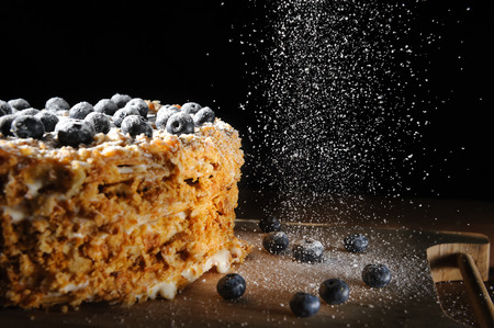 layered cake, Napalion cake, puff cake with blueberry sprinkled with powdered sugar, on a rough wooden backing, menu background Stock Photo