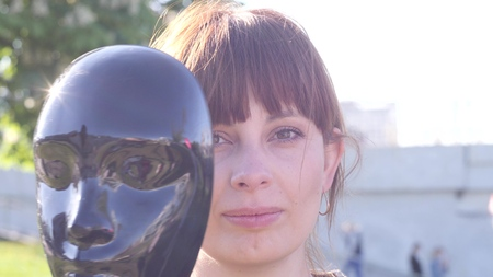 portrait of a young pretty charismatic woman who hiding her face behind the black mask and then sets it aside and smiles against the background of the city, close up video in slow motion in 4K Stock fotó