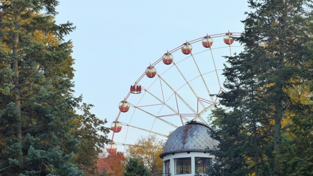 Ferris wheel rotates in a park in the foreground roof observatory Foto de archivo